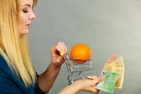 Buying healthy food, vegetarian, gluten free, vegan products. Woman holding shopping cart with orange inside and euro money in cash Stock fotó