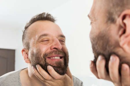 Mature adult man investigating his unshaved facial hair. Guy thinking about shaving his short beard