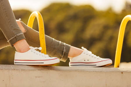 Woman feet wearing white sneakers, casual shoes. Female relaxing outdoors. Footwear perfect for warm weather.