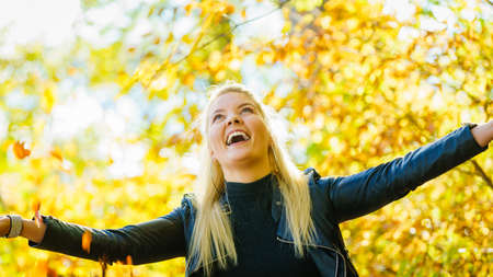 Woman relaxing in autumn park throwing leaves up in air with arms raised up. Blonde girl in colorful forest foliage outdoor.