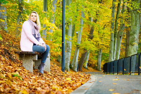 Blonde sad woman in autumnal park at sunny day Banco de Imagens