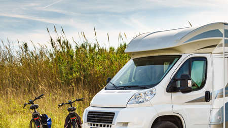 Camper, recreational vehicle and two bicycles. Camping on nature. Holidays and travel in motorhome. Standard-Bild