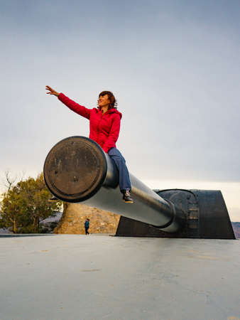 Tourist woman at Battery de Castillitos in Spain Cartagena, Cabo Tinoso. Military cannon for coast defense, massive naval gun batteries. Place to visit.