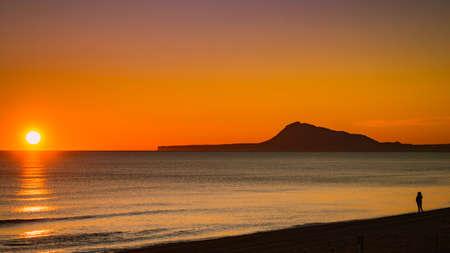 Person silhouette on beach looking at horizon enjoying sunrise. Gandia beach, Valencia Spain. Montgo mountain massif silhouetted on horizon.