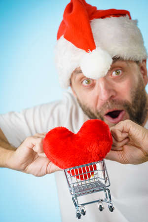 Man wearing santa claus hat holding shopping basket cart with red heart, on blue. Christmas, charity sharing concept.