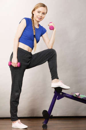 Teenage young woman working out at home with small light dumbbells. Training at home, being fit and healthy, presenting sit ups bench