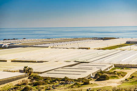 Spanish landscape and view of sea coast with many plastic greenhouses on hills. Almeria region, Andalusia