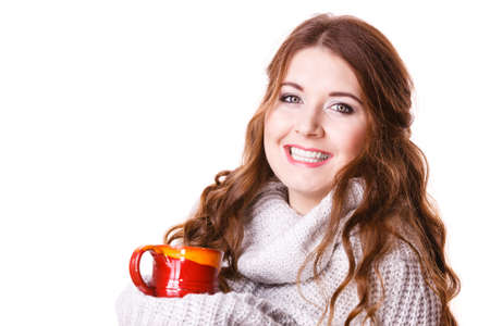 Woman wearing warm clothing gray sweater holding nice red mug of warm beverage tea or coffee, isolated on white. Standard-Bild