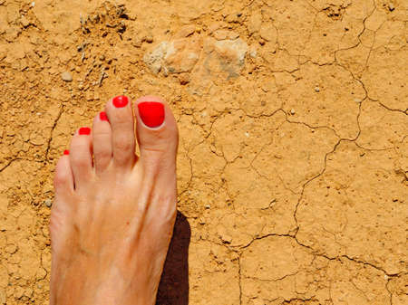Woman suntanned feet with red nail polish on beach, dry ground. Girl relaxing enjoying sun on sunny summer day.