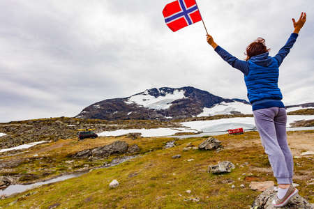 Woman holds norwegian flag in mountains, van with canoe on top roof in distance. National tourist scenic route 55 Sognefjellet, Norway 版權商用圖片