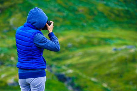 Tourist woman enjoy mountains landscape, taking travel photo with camera. National tourist scenic route 55 Sognefjellet, Norway 版權商用圖片