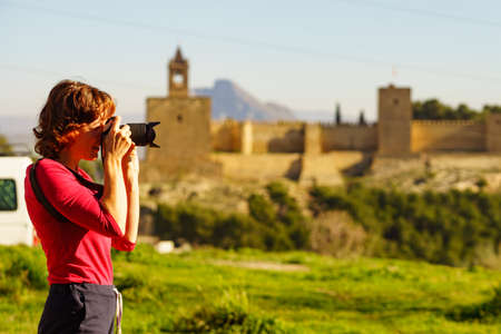 Mature female tourist with camera taking travel photos in Antequera city, Alcazaba fortress in the distance. Province of Malaga, Andalucia Spain.