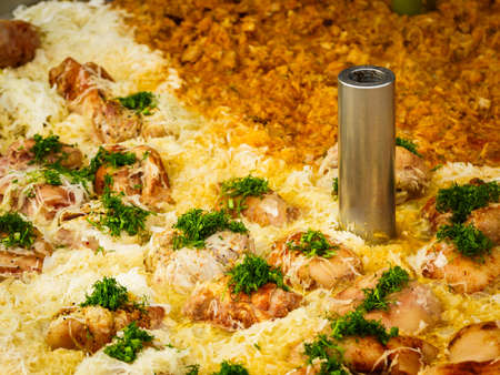 Cooked cabbage and many pork knuckle topping with fresh green dill in big pot. Polish traditional cuisine at the food festival. Standard-Bild