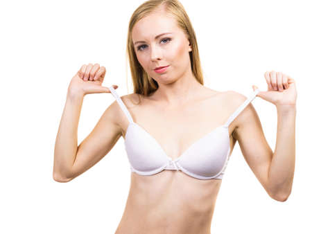 Young slim woman holding bra strap. Straps keep falling down problem. Female in lingerie. Bosom and underwear concept.
