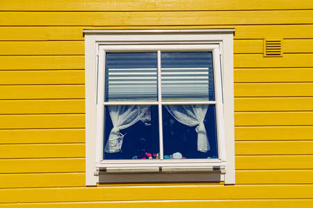 Window on yellow wall house, fasade architecture detail, scandinavian building