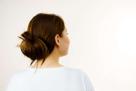 Young woman long brown hair wrapped in bun. Back view