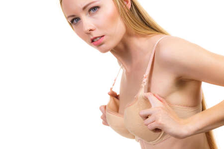 Young woman small wearing too big bra. Female wrong size lingerie. Bosom, brafitting concept. Breasts enlargement.