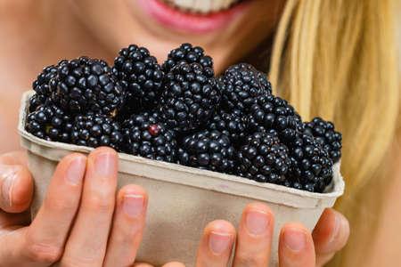 Girl holding fresh blackberry fruits in paper box. Healthy seasonal fruit, organic nutrition. Stock Photo