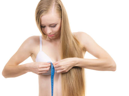 Young woman wearing white bra using tape measure to check the measurements of her chest breasts. Bosom, brafitting and underwear concept.