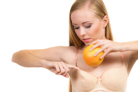 Slim young woman small puts big orange fruit in her bra. Breast enlargement size correction concept.