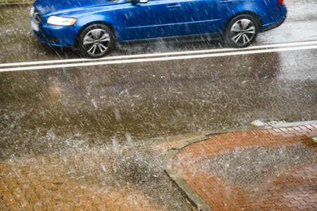 Rain in city. Car driving on street during downpour. Water splashes, spills on roadway. Autumn season Foto de archivo