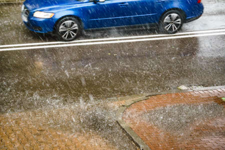 Rain in city. Car driving on street during downpour. Water splashes, spills on roadway. Autumn season