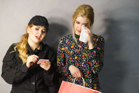 Shoplifting is a crime. Teenage girl being caught on stealing clothes by female security guard. Customer thief Stock Photo