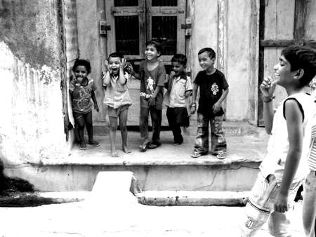 gujarat: kids playing and looking on something in the streets of sankheda, gujarat, india
