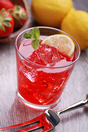 alcoholic beverages: cocktail of strawberry and lemon with ice on the table Stock Photo