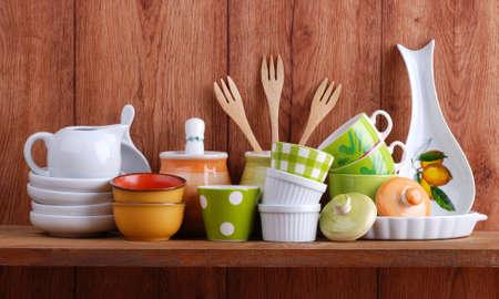 colorful ceramic kitchen utensils on wooden shelf