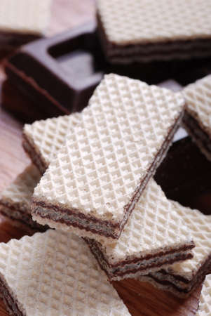 heap of wafers with chocolate cream on wooden table