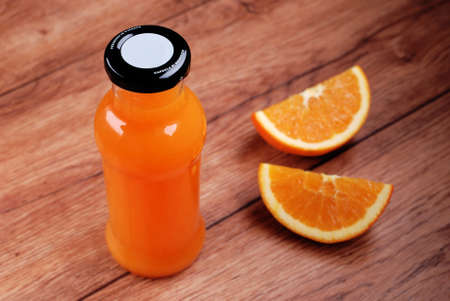 orange juice in a glass bottle on wooden table photo