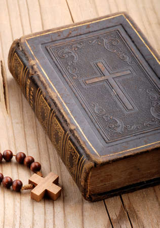 religious book with rosary on the wooden table Standard-Bild