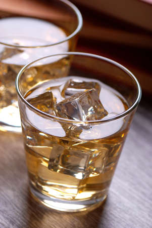 whiskey with ice in glasses photographed against the light photo