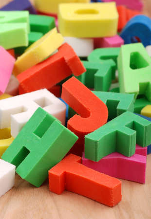 pile of colored letters of the alphabet on wooden table photo