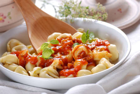 stuffed tortellini: tortellini with tomato sauce garnished with mint leaves
