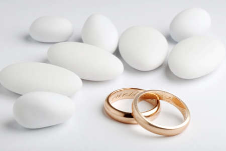 wedding rings with jordan almonds on white background