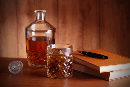 whiskey on the rocks, books and pen on the table photo