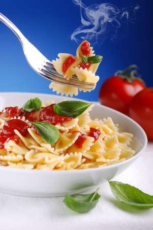 macaroni: pasta met tomatensaus smeulende met blauwe hemel achtergrond Stockfoto