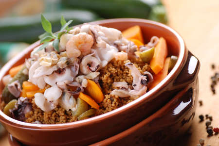 couscous with seafood in earthenware bowl Standard-Bild