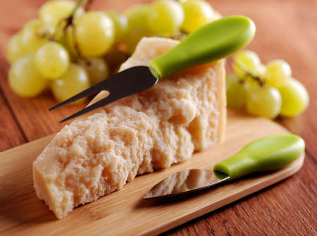boxcutter: portion of parmesan cheese with bunch of grapes