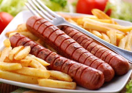 Roasted frankfurters with French fries on dish photo