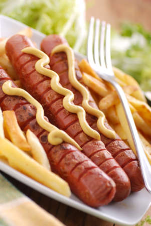 roasted frankfurters seasoned with mustard served with French fries on dish photo