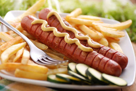 mustard: roasted frankfurters seasoned with mustard served with French fries on dish