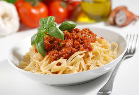 tagliatelle with meat sauce garnished with basil leaves Standard-Bild
