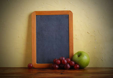 the blackboard with apple and grapes photo