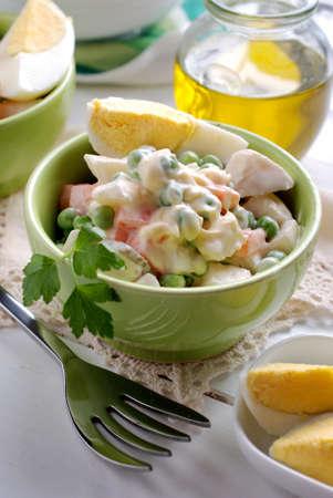 huzarensalade: Russische salade met gekookte eieren binnen groene kom