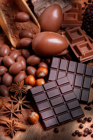 Easter eggs and assorted chocolate on wooden table Standard-Bild