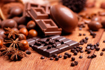 chocolate background: Easter eggs and assorted chocolate on wooden table Stock Photo
