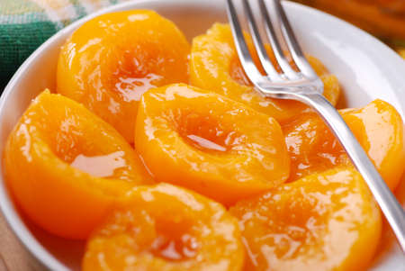 homemade peaches in syrup in white bowl photo
